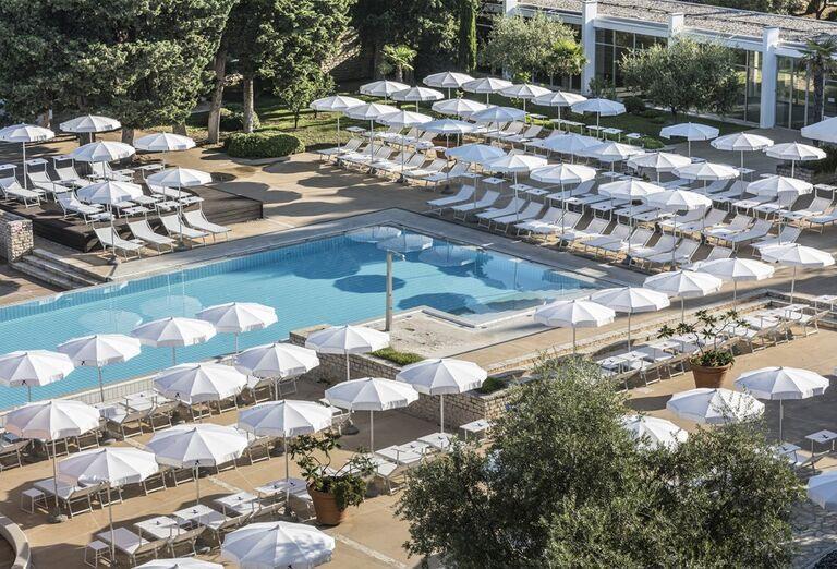 Ležadlá a slnečníky pri bazéne v areáli hotela Falkensteiner Club Funimation