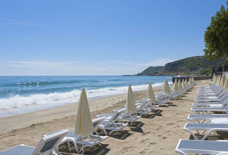 Pieskov pláž s ležadlami pred hotelom Floria Beach