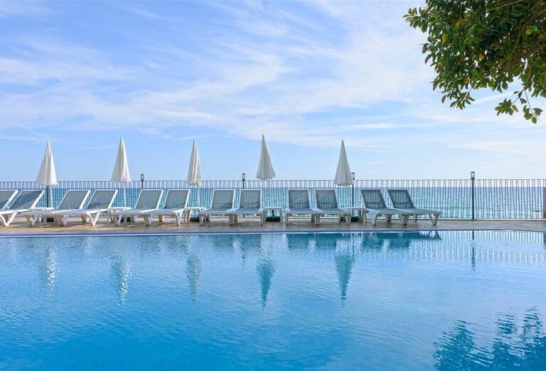 Bazén s ležadlami a slnečníkmi pred hotelom Floria Beach