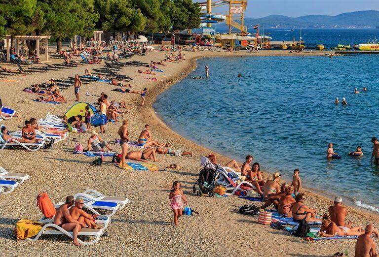 Ľudia na pláži pred hotelom Olympia Sky