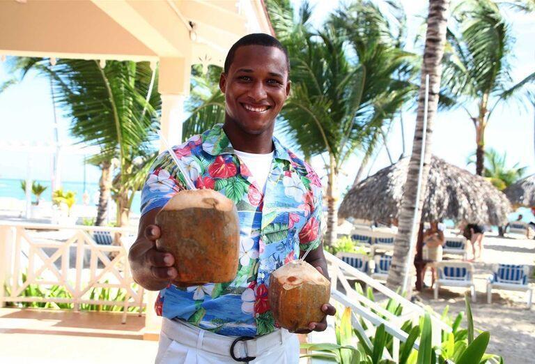Čašník ponúkajúci exotický nápoj v hoteli Luxury Bahia Principe Ambar