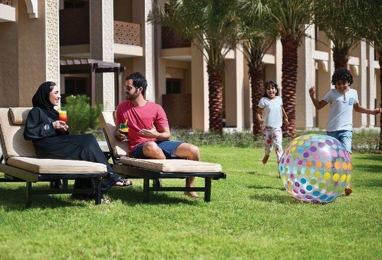 Rodičia pijú drink a deti sa hrajú s loptou