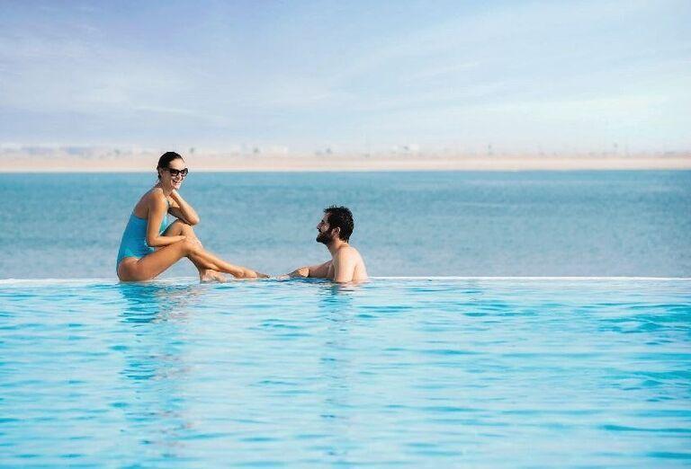 Muž v bazéne a žena na kraji bazéna