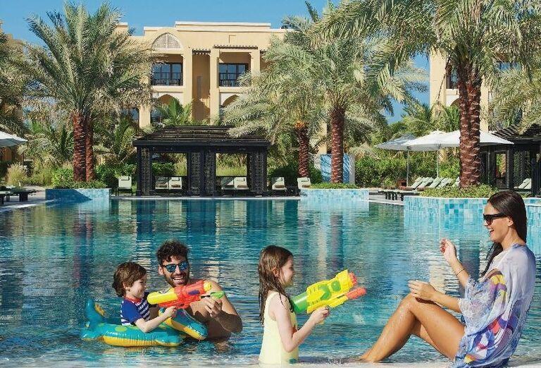 Rodinka v bazéne sa hrá s vodnými pištoľami