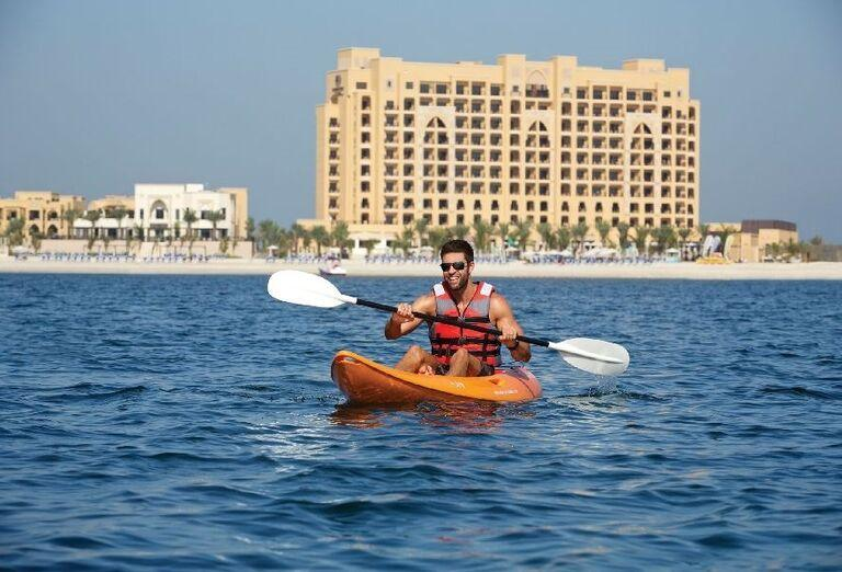 Muž na kanoe pred hotelom Doubletree by Hilton Resort & Spa Marjan Island
