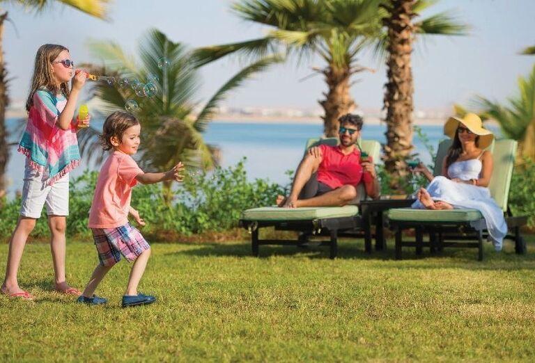 Rodičia oddychujú a deti sa hrajú s bublifukom