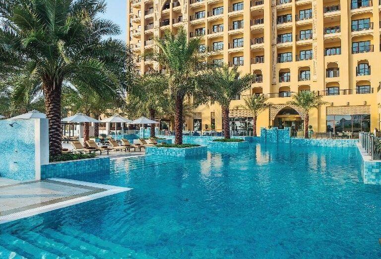 Bazén v okolí s palmami v hoteli Doubletree by Hilton Resort & Spa Marjan Island