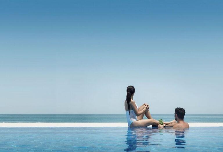 Párik v bazéne pozerajúci sa na more