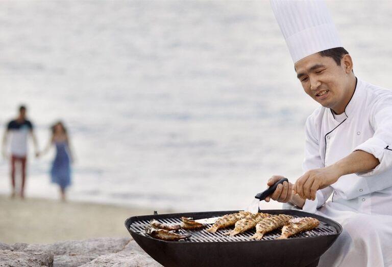 Kuchár pripravuje jedlo na grile na pláži pri hoteli Waldorf Astoria Dubai Palm Jumeirah