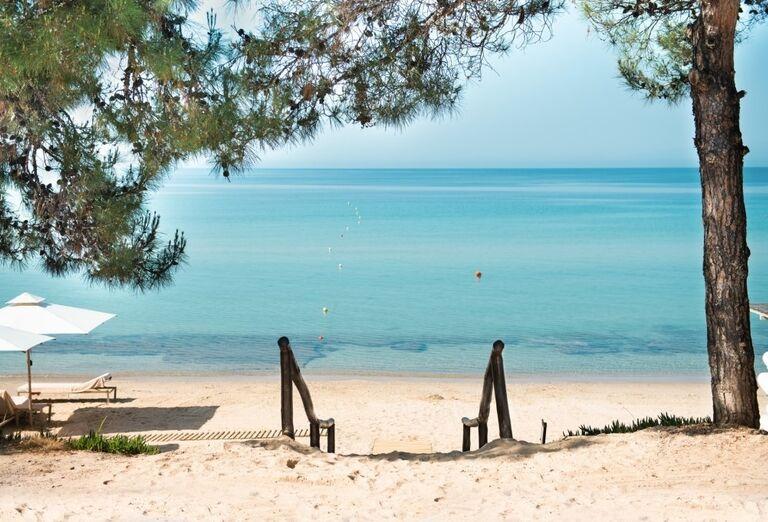 Pohľad na pieskovú pláž pred hotelom Ikos Oceania