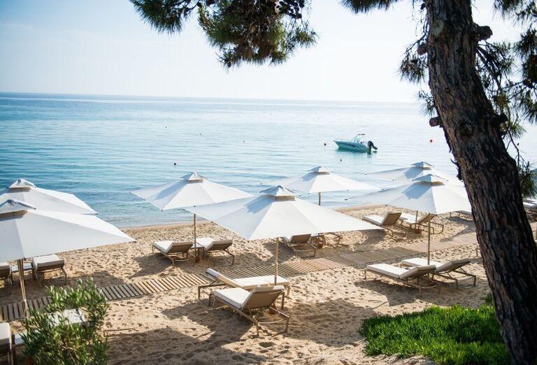 Ležadlá na pláži pri hoteli Ikos Oceania