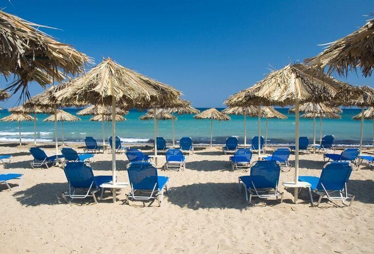 Ležadlá a slnečníky na pláži pred hotelom The Lesante Luxury Hotel & Spa