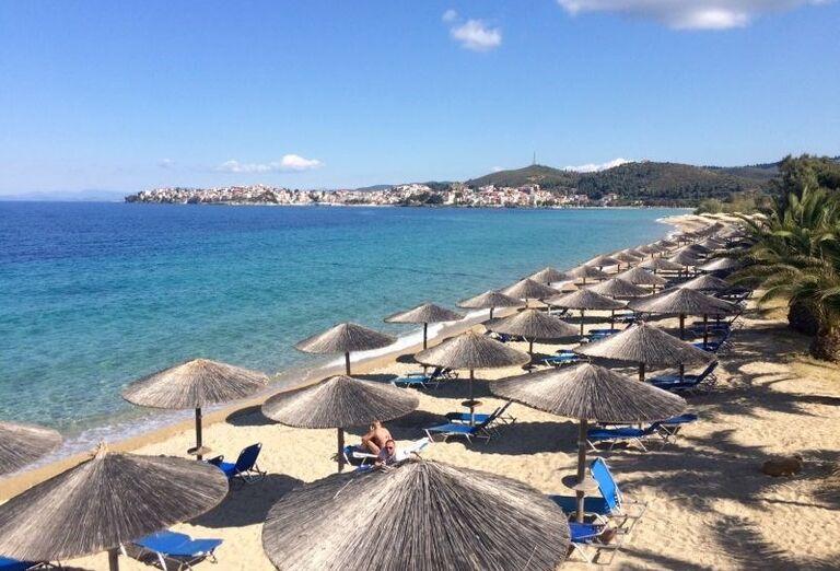 Pláž so slamenými slnečníkmi pred hotelom Porto Carras Sithonia